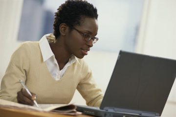 Young Woman with Newspaper Using Laptop --- Image by © Royalty-Free/Corbis